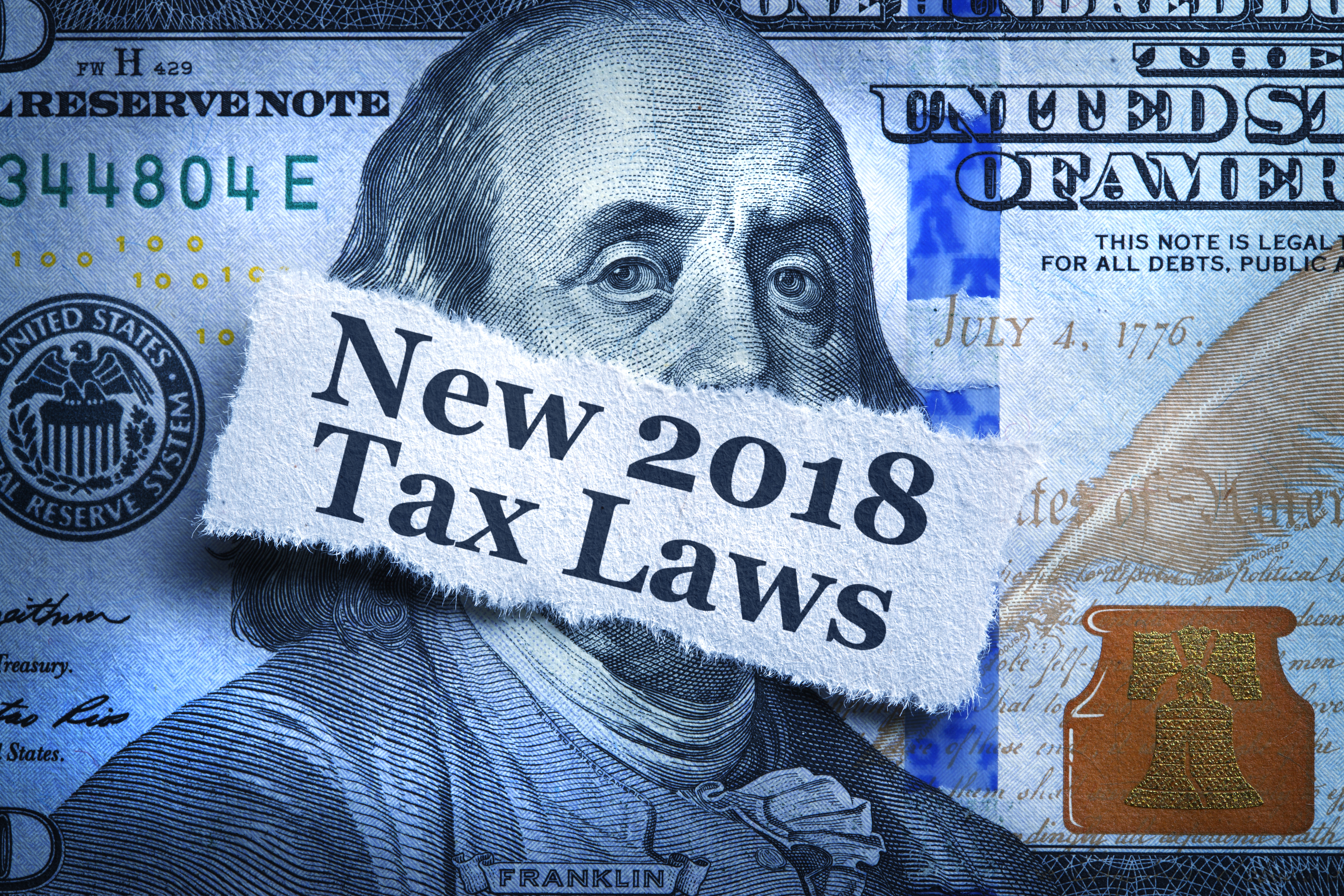 A torn piece of paper telling of the new 2018 tax laws rests on top of a one hundred dollar bill.